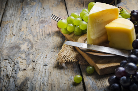 Wine and cheese on rustic wooden table photo