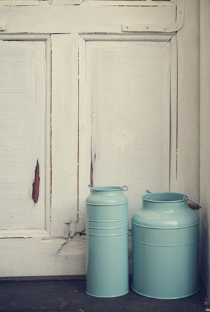 Vintage blue milk canisters in front of rustic door. photo