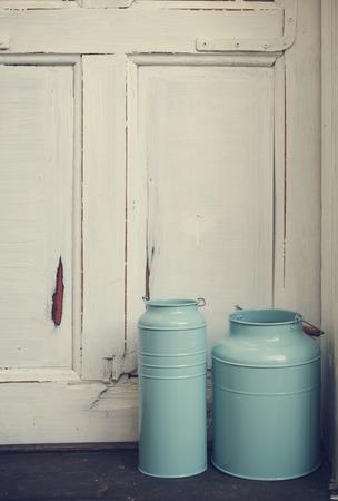 Vintage blue milk canisters in front of rustic door. photo