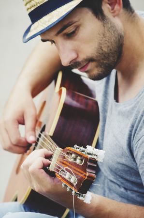 남자 거리에서 기타를 재생합니다. 복고 스타일입니다. 스톡 콘텐츠