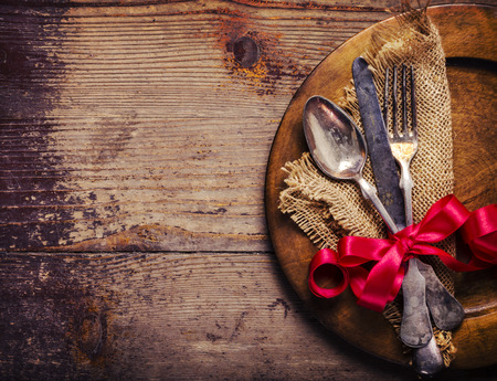 grunge flatware: Vintage silverware decorated with red ribbon