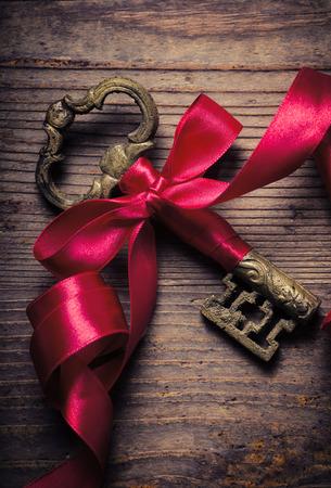 Oude sleutel versierd met rood lint Stockfoto
