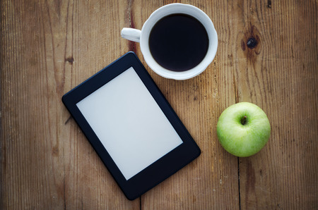 E-book reader, green apple and coffee cup on wooden table