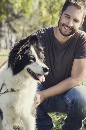 friends hugging: Man with his dog playing in the park Stock Photo