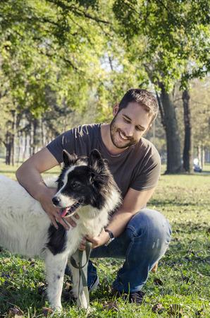 男と彼の犬が公園で遊んで