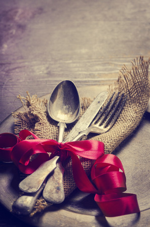 Vintage valentine table settings decorated with red ribbon. Image is filtered.