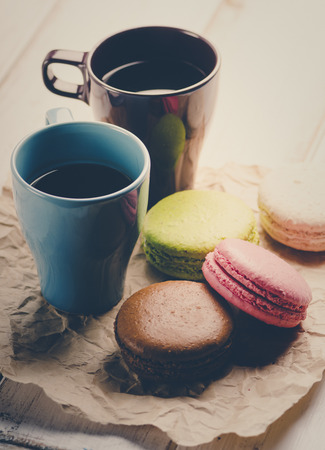 Two cup of coffee and colorful macaroons. Retro filter. photo