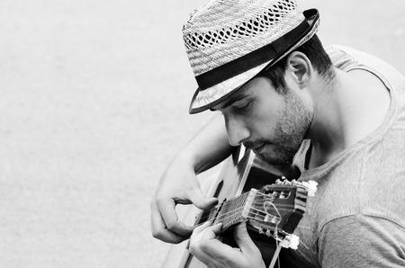 Черно-белая фотография человека с гитарой.