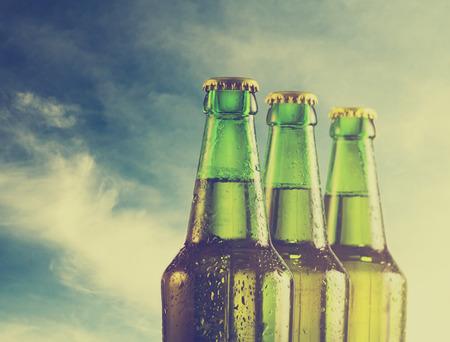 botellas de cerveza: Botellas de cerveza en la playa. Filtro Retro. Foto de archivo