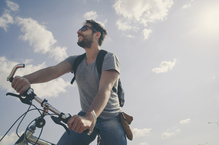 レトロなスタイルで自然の中で自転車に乗る男。 写真素材