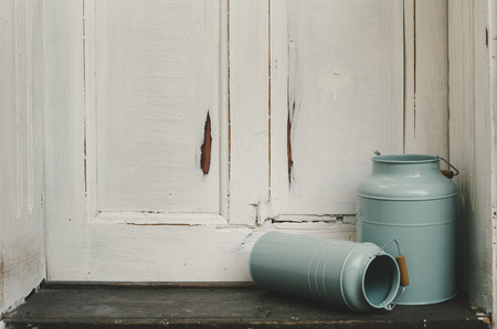 coutryside: Vintage blue milk canisters in front of rustic door.