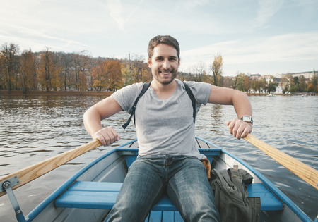 man holding: happy smiling man rowing on the river