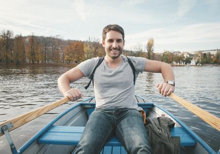 Hombre sonriente feliz remo en el río Foto de archivo - 40907753