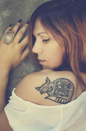 Портрет стильный молодой женщины с татуировкой.