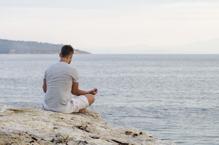 Young man sitting on the coast and meditating