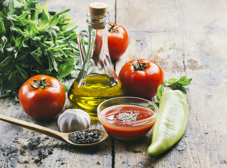 Olive oil, tomato and herbs on rustic wooden table
