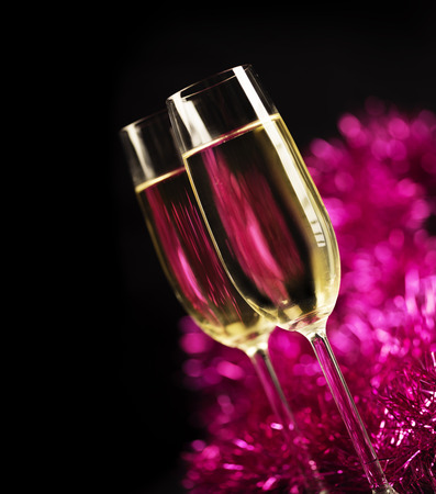 purple: Two champagne glasses in front of purple sparkling background