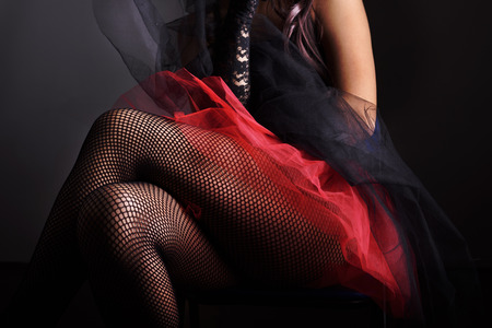 erotic fantasy: Sexy female legs in net stockings and red skirt
