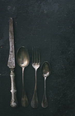 spoons: Vintage silverware on black rustic background. Retro filter. Stock Photo