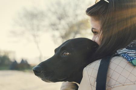 若い女性は彼女の犬にキスします。レトロなフィルターです。