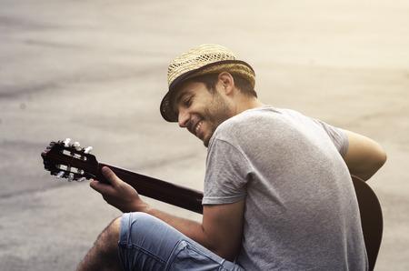 거리에서 기타를 연주하는 사람 (남자). 복고 스타일입니다. 스톡 콘텐츠