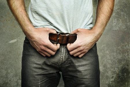 male hand: Man in jeans with fashionable leather belt Stock Photo