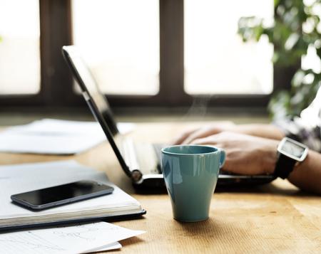 Bureau de travail avec un ordinateur portable, notbook et coffe cup.