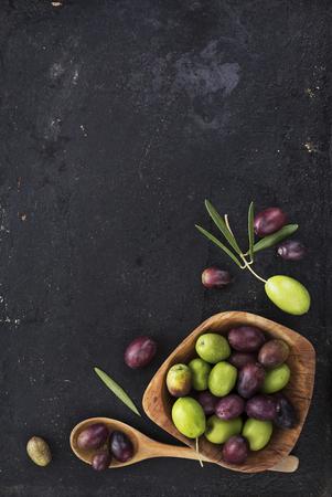 olive green: Fresh olives on black rustic background Stock Photo