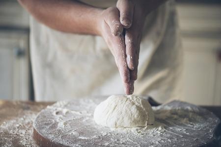 haciendo pan: hornear pan hombre en la cocina. Foto de archivo