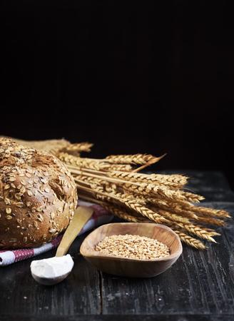 copyspace: Bread and wheat ears on dark wooden board with copyspace