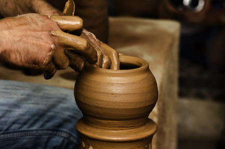 shaping: Potter shaping clay on the pottery wheel