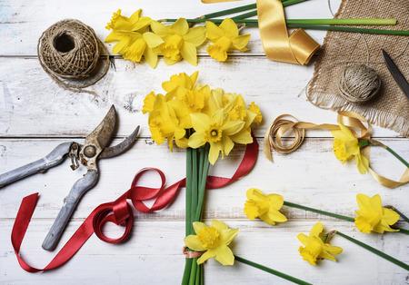 arreglo floral: Ramo de narcisos y herramientas de jardinería en la mesa de madera rústica Foto de archivo