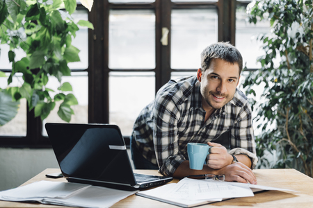 smiling businessman: Young man working in cool workspace. Modern office concept.