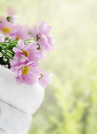 productos naturales: toallas limpias blancas y flores frescas con fondo verde natural