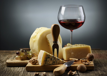 Cheese and red wine on wooden board. Standard-Bild