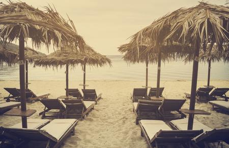 skiathos: Sun umbrellas and sunbeds on beautiful sandy beach. Retro filter.