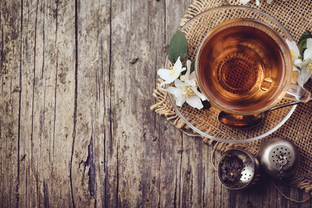 Cup of tea and jasmine flower on rustic wooden table, Top view.