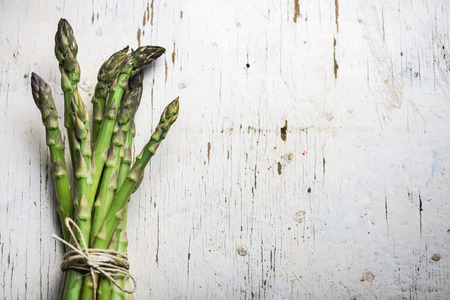 Fresh green asparagus on rustic white table