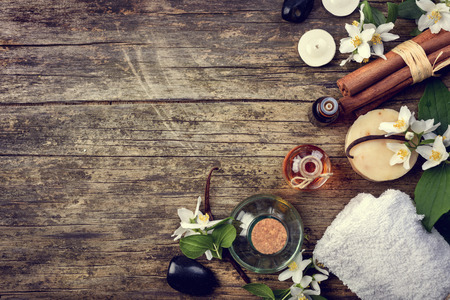 Essential oils with jasmine, cinnamon and vanilla on rustic wooden table, retor style image.