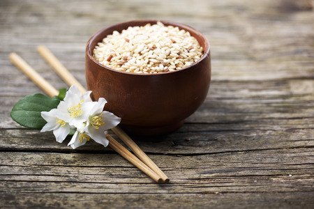 Rice and jasmine flower onrustic wooden table Stock Photo