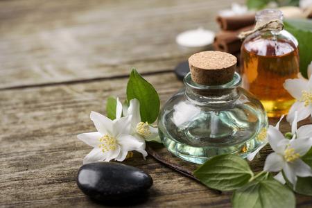 Ätherische Öle mit Jasmin, Zimt und Vanille auf rustikalen Holztisch,