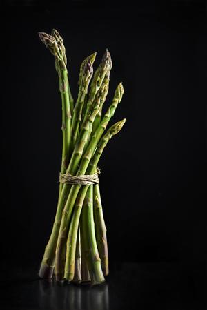 food still: Fresh asparagus on black background Stock Photo