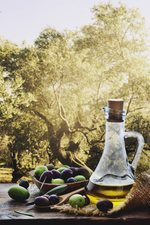 gastronomy: Bottle of olive oil and fresh olive fruit on wooden table in front of mediterranean olive trees Stock Photo
