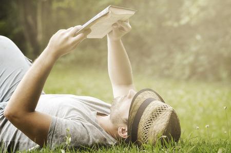 personas leyendo: Joven tendido en la hierba, relajante y leer un libro. filtro retro Foto de archivo