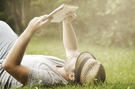 people relaxing: Young man lying in the grass, relaxing and reading a book. Retro filter Stock Photo