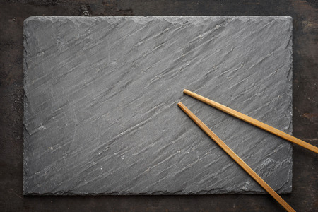 granite: Black sushi slate board with wooden chopsticks with copyspace. Top view. Stock Photo