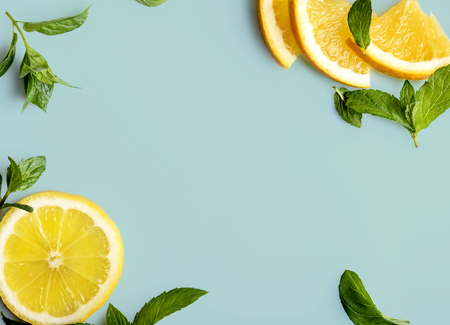 Citrus slices and mint herbs frame on retro mint background with copyspace