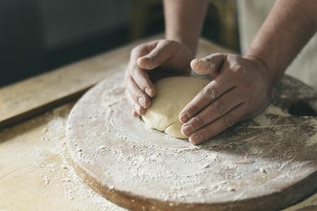 haciendo pan: las manos del panadero hacer pan en la tabla de madera. Foto de archivo
