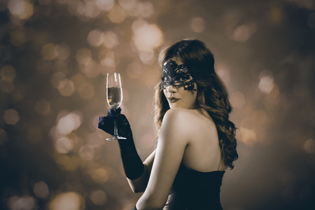 evening glow: Beautiful woman with venetian carnival mask holding champagne glass and toasting. Lady at evening event party in front of golden bokeh lights. Holiday and new year celebration concept.