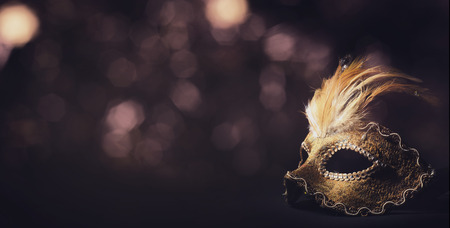 Golden venetian ball mask in front of the night bokeh lights. Masquerade party or holiday event celebration concept. Фото со стока - 65571056